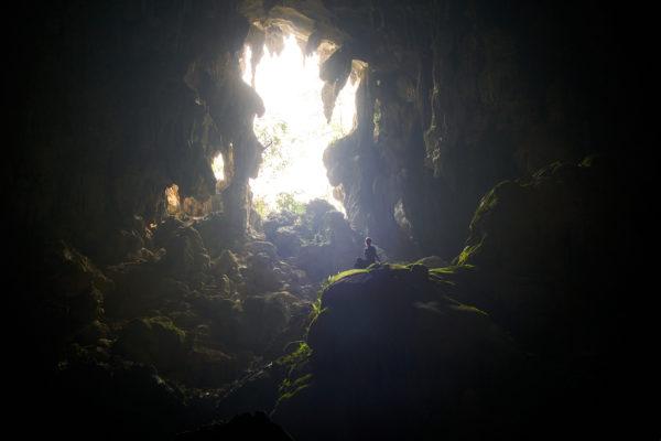 Pvk Photo | Photographe Professionnel | Femme assise en contre-jour dans la grotte de tham Poukham à Vang Vieng au Laos