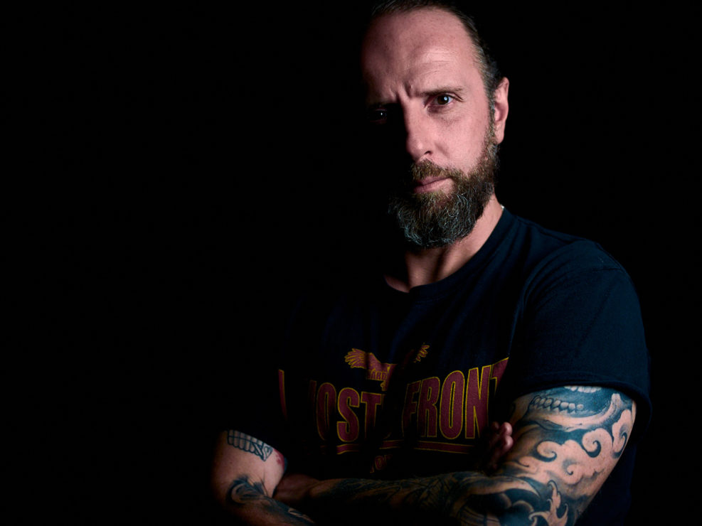 Portrait studio sur fond noir d'un homme avec une barbe et des tatouages, type personal branding