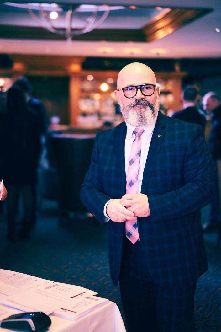 Portrait corporate naturel d'un homme en costume et avec une cravate rose et bleue