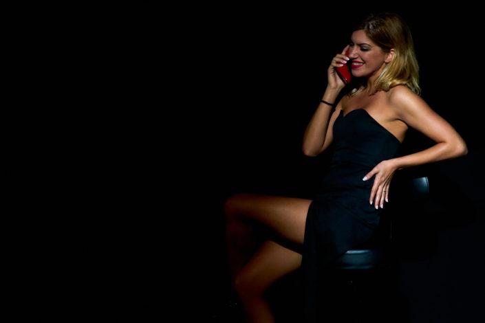 Pvk Photo | Photographe Professionnel | Femme fatale en robe noire sur scène avec une téléphone rouge