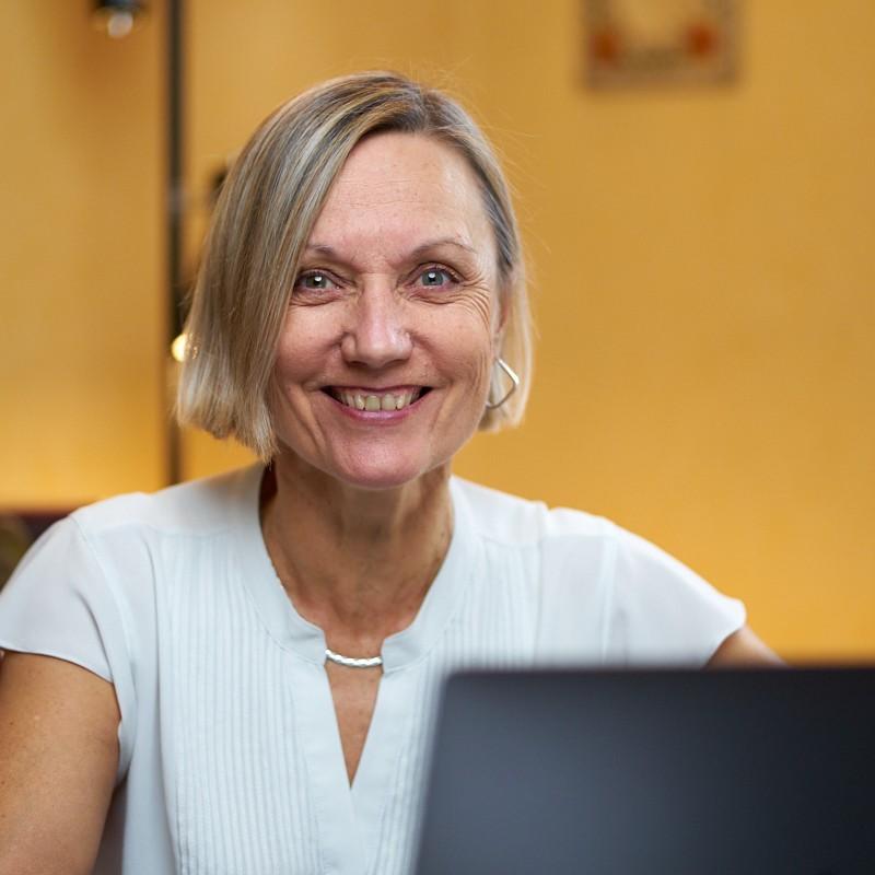 PVK Photo | Portrait Corporate | Femme souriante en blanc avec son ordinateur