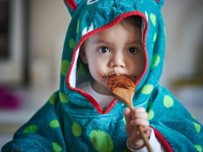 enfant lechant une cuillere de chocolat