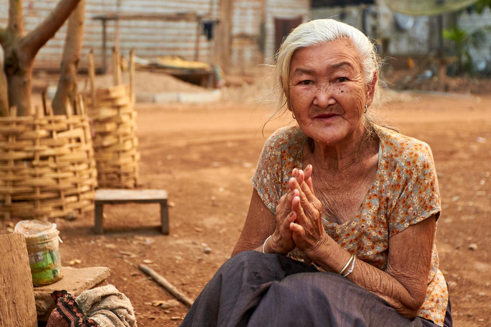 Pvk Photo | Photographe Professionnel | Mamie laotienne au village de Nam Nga en train de faire le salut Laotien