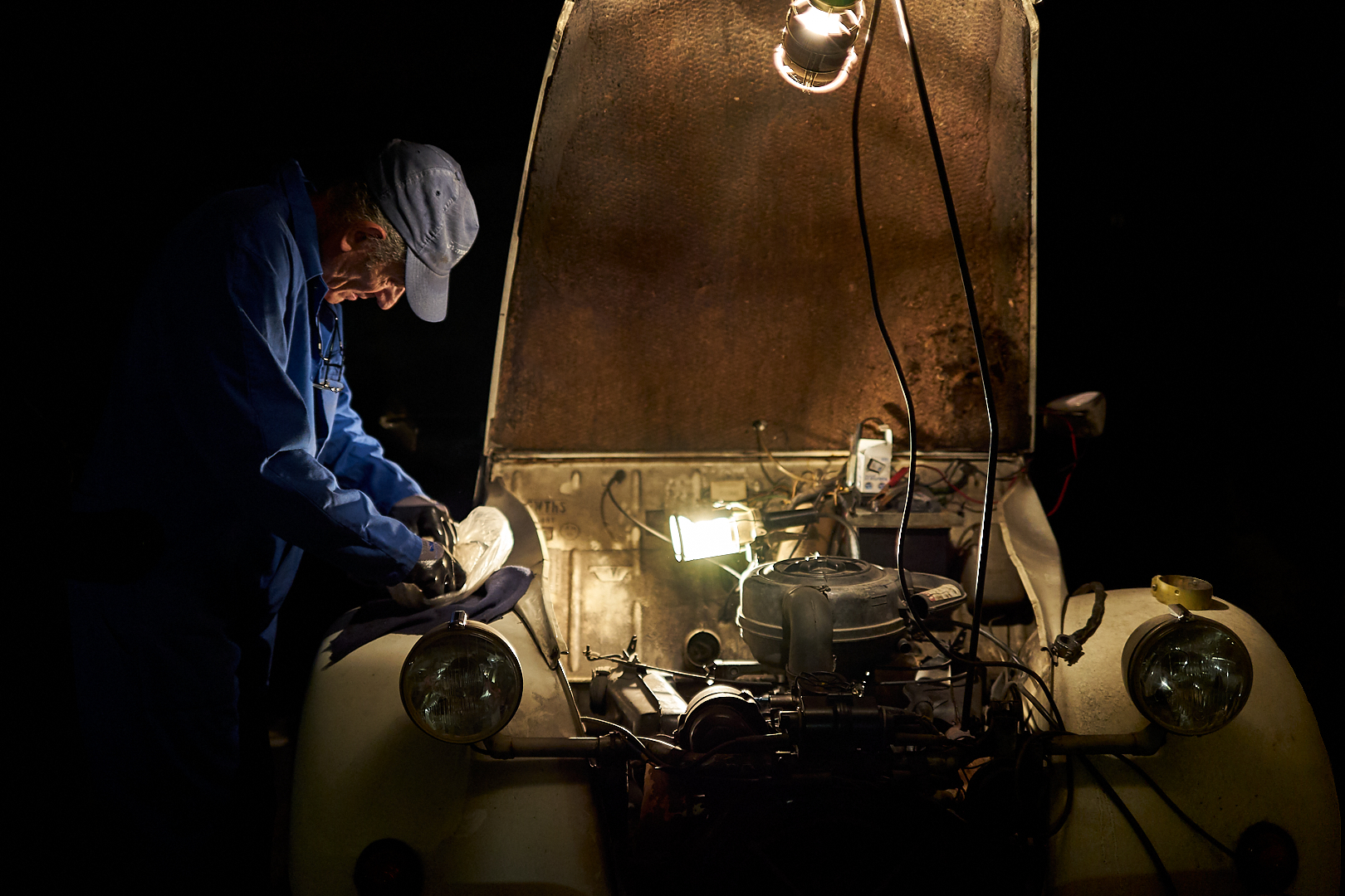 Vieux garagiste en train de réparer une 2cv avec le capot ouvert