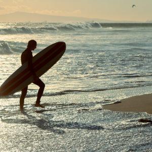 Pvk Photo | Surfeur sortant de l'eau en contre jour Huntington Beach, Californie