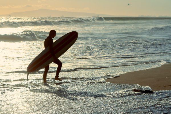 Pvk Photo | Surfeur sortant de l'eau en contre jour Huntington Beach, Californie